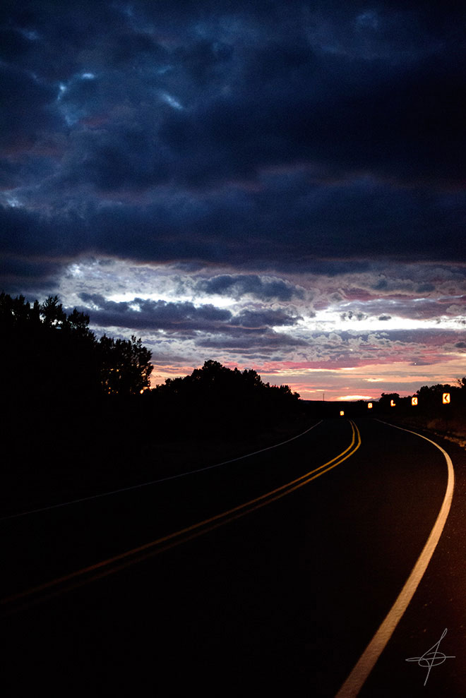 Road leading into the sunset in Santa Fe, NM. By photographer John Ussenko