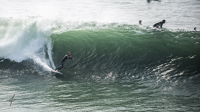 Unknown surfer grabs a huge wave at the Huntington beach pier during a 10-12ft swell. Lifestyle photographer, John Ussenko captures the action.