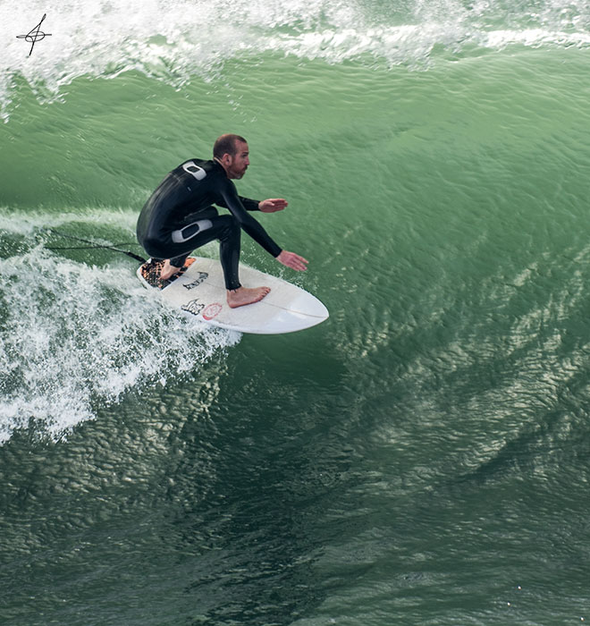 Close up of surfer getting into a barrel at Huntington Beach.
