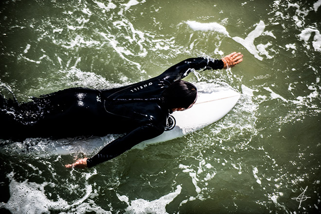 Surfer Paddling Out at Huntington Beach Pier towards 10-12ft swells captured by lifestyle photographer, John Ussenko.